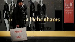 Man walking in front of Debenhams window