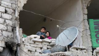 Children look out from a destroyed home in Aleppo, Syria