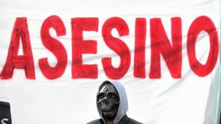 in_pictures A man with a mask stands before a placard reading
