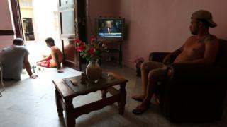 Un cubano ve el discurso de Trump desde el televisor de su casa mientras dos jóvenes juegan ajedrez en el portal de la casa.
