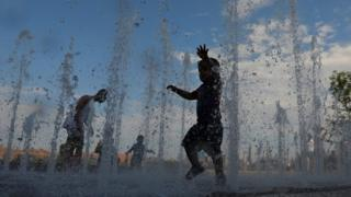 Children play in a New York water feature