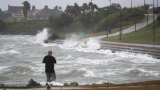walks near the bay waters as they churn from approaching Hurricane Harvey on August 25, 2017 in Corpus Christi, Texas