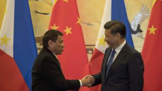 China's President Xi Jinping and Philippines president Rodrigo Duterte shaking hands.