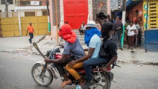 Three men on motorcycle, two of them showing machetes, are heading to block the street leading to the house of the President of Haiti, Jovenel Moise, during a new day of protests in Port-au-Prince, Haiti, 24 February 2020