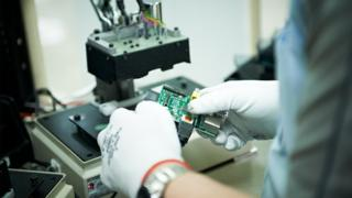 A person holding a circuit board