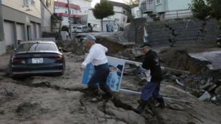 Imagem mostra uma das ruas afetadas pelo terremoto na província de Hokkaido, no Japão, onde dois homens carregam placa de político