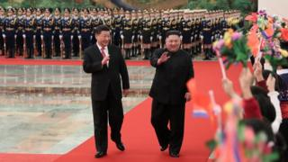 "North Korean leader Kim Jong Un (R) and China""s President Xi Jinping waving to children"