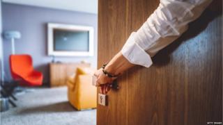 Hand holding hotel room door open