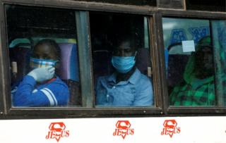 People wearing face masks on board a bus look out the window on 27 April.