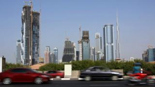 Cars drive past skyscrapers under construction in the Gulf emirate of Dubai on November 27, 2009
