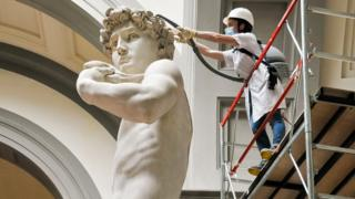 A restorer cleans the head of Michelangelo's David statue