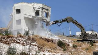 Israeli army excavator demolishes a building in Wadi Hummus, in the occupied West Bank (22 July 2019)