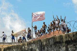 Inmates stand on a roof inside the State Penitentiary of Alcacuz in Nisia Floresta near Natal, Rio Grande do Norte, Brazil