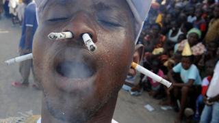 Un homme fume la cigarette avec le nez et les oreilles lors du carnaval annuel des Popo à Bonoua.