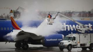 Workers remove ice from an aeroplane in Chicago, which is expected to be one of the worst affected cities