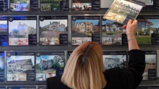 woman looks in estate agent window