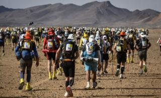 People compete in the fourth stage of the 34th edition of the Marathon des Sables between Jebel El Mraier and Rich Mbirika in the southern Moroccan Sahara desert, on Wednesday 10 April 2019