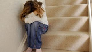 Young girl (6 years of age) sits on the landing of a staircase and covers her face