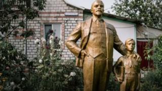 Una estatua de Lenin y de un niño frente a una casa