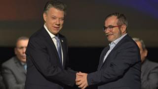 サントス大統領(写真左)とロンドニョFARC最高司令官が握手した際には、出席者は「我々にはできた」との言葉を繰り返した(24日、ボゴタ)