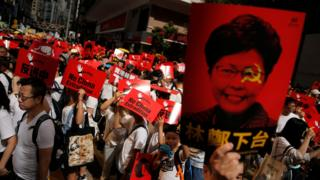 Demonstrators hold up a signs during a protest to demand authorities scrap a proposed extradition bill with China