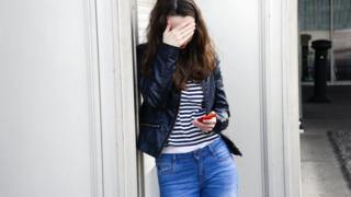 Teenage cyberbullying. 16-year-old girl who has been upset by an insulting text message