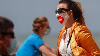 A tourist wearing a protective face mask walks along the beach in Belgium as it was added to the UK's quarantine list