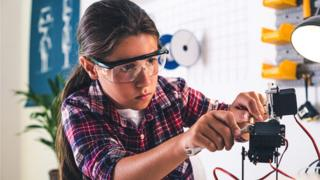 Girl in a robotics laboratory adjusts the robot arm model