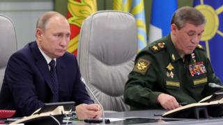 الرئيس الروسي فلاديمير بوتين (يسار) يجلس بجانب نائب وزير الدفاع في مركز التحكم للدفاع الوطني