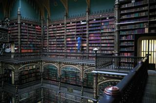 An employee selects a book from the shelves of the Royal Portuguese Cabinet of Reading in Rio de Janeiro, Brazil
