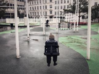 A child sits on the swings in an empty playground