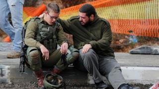 An Isreali soldier is consoled as Israeli forces and forensic experts inspect the site of a Palestinian drive-by shooting attack outside the West Bank settlement of Givat Asaf, northeast of Ramallah, on December 13, 2018