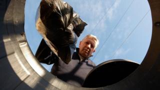 man putting rubbish in bin