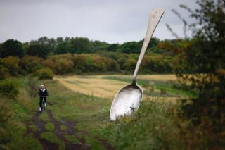 in_pictures A person cycles past a large sculpture of a spoon on the edge of a field
