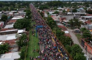 An aerial view of a road filled with migrants stretching back into the distance