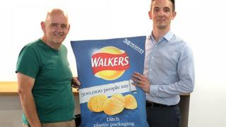 "Campaigner Geraint Ashcroft (l) meets Duncan Gordon from Walkers' owner PepsiCo to present a ""ditch the plastic"" giant Walkers crisp packet"