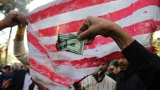 An Iranian protester burns a US banknote