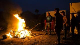 Migrants burn their bikes in a bonfire at the Jungle camp, Calais, northern France. Photo: 24 October 2016