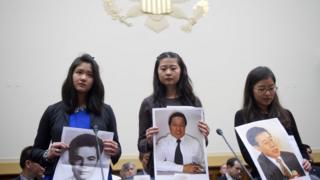 彭明的女儿(图左)和王炳章的女儿(图右)在美国国会一个听聆会手持她们父亲的照片。