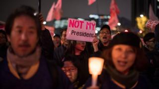 """Demonstrators hold candles and a poster saying """"not my president"""" during an anti-government protest in central Seoul (November 19, 2016)"""