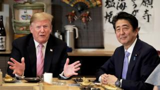 "U.S. President Donald Trump talks with Japanese Prime Minister Shinzo Abe during a couples dinner with first lady Melania Trump and Abe""s wife Akie in Tokyo"