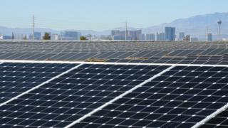 The Las Vegas Strip is shown behind solar panels during a dedication ceremony to commemorate the completion of the 102-acre, 15-megawatt Solar Array II Generating Station at Nellis Air Force Base on February 16, 2016 in Las Vegas, Nevada.