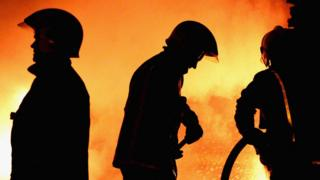 fire crews in silhouette against a fire