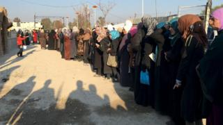 Lines of people queue in Muadhamiya, Syria, for aid