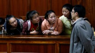 Taiwanese and Chinese nationals arrested on suspicion for involvement telecommunications fraud, listen to their translator as they sit inside the Milimani Law Courts before they were acquitted of cyber crime in Kenya's capital Nairobi (August 5, 2016)