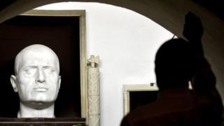 一名游客向墨索里尼的雕像作法西斯主义敬礼。