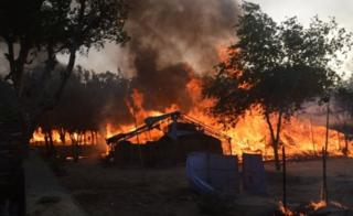 Former homes of Indian members of a sect burn following clashes with police during an eviction at the Jawahar Bagh park in Mathura on June 2, 2016