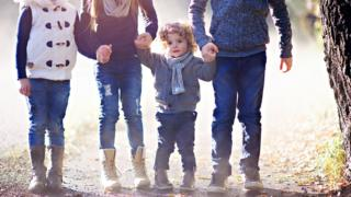 stock image of a little boy holding hands with his two older siblings, and a fourth child alongside