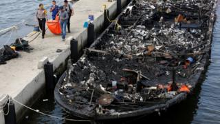 The remains of a victim is carried away after a fire ripped through a boat carrying tourists to islands north of the capital, at Muara Angke port in Jakarta, Indonesia on 1 January 2017