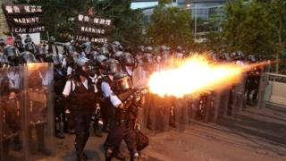 Police officers in Hong Kong fire tear gas at protesters.